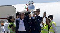 Cristiano Ronaldo (vpravo) s trofejí pro mistry Evropy při výstupu z letadla. Vlevo je trenér Portugalců Fernando Santos.