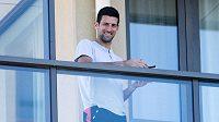 Novak Djokovič se usmívá z balkónu svého luxusního pokoje v Adelaide. Většina ostatních tenistů v Melbourne takovou pohodu nemá.