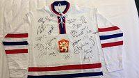 I v druhém kole dražby je replika dresu československé hokejové reprezentace z MS 1972 v Praze s podpisy současného výběru trenéra Růžičky.