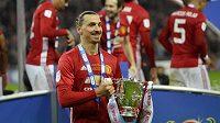 Radostný výraz Zlatana Ibrahimoviče, když drží v ruce trofej pro vítěze anglického Ligového poháru.