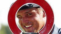Bryson DeChambeau se dívá skrz trofej pro vítěze Rocket Mortgage Classic v Detroitu.