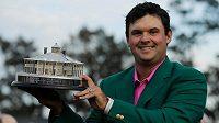 Vítěz Patrick Reed pózuje v tradičním zeleném saku s trofejí pro vítěze Masters.