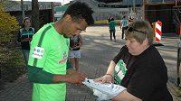 Obránce Werderu Brémy Theodor Gebre Selassie se po tréninku podepisuje fanouškům.