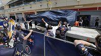 Mechanici sundávají s pomocí jeřábu nepojízdný monopost před garáží Red Bullu při testech v Bahrajnu.