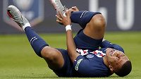 Hvězda PSG Kylian Mbappé se svíjí v bolestech na trávníku po faulu Loica Perrina ze St. Etienne.