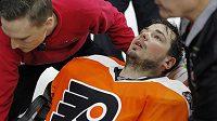 Gólman Philadelphie Michal Neuvirth v péči zdravotníků poté, co během utkání NHL s New Jersey zkolaboval.