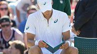 Kanadský tenista Vasek Pospisil si čte poznámky během výměny stran ve Wimbledonu.