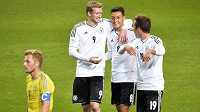 Andre Schürrle (vlevo) slaví s Mesutem Özilem (uprostřed) a Mariem Götzem gól proti Švédsku. Dole zklamaný kapitán Švédů Sebastian Larsson.