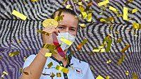 Olympijská vítězka v tenisové čtyřhře Barbora Krejčíková ukazuje zlatou medaili fanouškům.