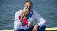 Skifař Ondřej Synek ukazuje bronzovou medaili.