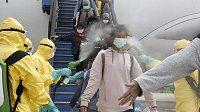 Indonésané, kteří přicestovali z čínského Wu-chanu, odkud se šíří nový typ koronaviru, procházejí na letišti v Batamu speciální dezinfekční očistou.