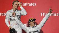 Britský jezdec Lewis Hamilton slaví vítězství ve Velké ceně USA před svým týmovým kolegou Nicem Rosbergem (vlevo).