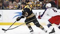 Pravé křídlo Bostonu Bruins David Pastrňák vede kotouč před obráncem Columbusu Blue Jackets Adamem Clendeningem během prvního zápasu druhého kola play off.