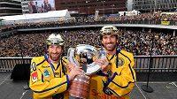 Dvojčata Joel (vlevo) a Henrik Lundqvistovi ve Stockholmu s pohárem pro mistry světa z loňského roku.