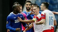 Rozčílení hráči Glasgow Rangers naháněli slávistu Ondřeje Kúdelu už na trávníku.