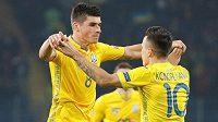 Střelec ukrajinského gólu Ruslan Malinovskij slaví se spoluhráčem Jevhenem Konopljankou.