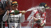Nico Rosberg (vlevo) sprchuje šampaňským Fernanda Alonsa.