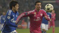 Acudo Učida (vlevo) ze Schalke bojuje o míč s hvězdným Cristianem Ronaldem z Realu Madrid.
