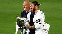 Trenér Zinédine Zidane a kapitán Realu Sergio Ramos pózují před fotografy s pohárem pro vítrěze La Ligy.