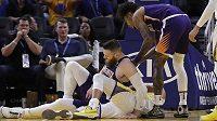 Basketbalista Phoenixu Suns Aron Baynes (vlevo) vstává poté, co spadl na hvězdu Golden State Warriors Stephena Curryho