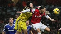 Brankář Petr Čech vyráží míč před dotírajícím Mesutem Özilem z Arsenalu.