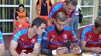 Obránce Milan Havel (vlevo), brankář Lukáš Zima a útočník Lukáš Juliš studují při autogramiádě bulletin české fotbalové reprezentace do 21 let pro mistrovství Evropy v Polsku.
