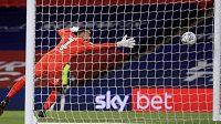 Brankář Brentfordu David Raya Martin se marně snaží zachytit míč por trestném kopu, který na jeho svatyni vyslal z dálky obránce Fulhamu Joe Bryan.