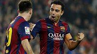 Hvězdy Barcelony - kapitán týmu Xavi Hernández (vpravo) a střelec Lionel Messi - slaví gól proti Seville.