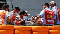 Zraněného Marca Márqueze odnášejí zdravotníci do sanitky na nosítkách.