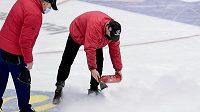 Pracovníci zimního stadionu opravují ledovou plochu.