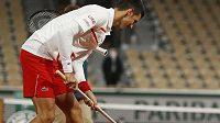 Novak Djokovič upravuje kurt před dalším pokračováním zápasu