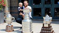 Hokejista Ryan O'Reilly s ročním synem a trofejemi z uplynulé sezony.