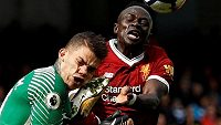 Gólman Manchesteru City Ederson Moraes inkasuje úder kopačkou do hlavy od Man´ho z Liverpoolu.