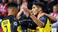 Fotbalisté Dortmundu Jadon Sancho (vlevo), Raphael Guerreiro a Achraf Hakimi oslavují během utkání základní skupiny Ligy mistrů na hřišti Slavie Praha.