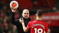 Trenér Manchesteru City Josep Guardiola podává balón fotbalistovi United Brunovi Fernandesovi v utkání 29. kola Premier League.