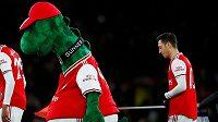 Německý fotbalista Mesut Özil kráčí za maskotem Arsenalu.