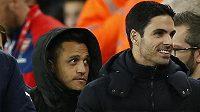 Alexis Sánchez sledoval šlágr proti Manchesteru City v kapuci jen z lavičky. Vpravo je jeho spoluhráč z Arsenalu Mikel Arteta.