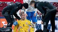 Dánský brankář Kasper Schmeichel ošetřovaný po srážce s Islanďanem Albertem Gudmundssonem.
