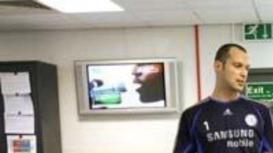 Petr Čech na návštěvě tréninkového centra. V popředí na lehátku útočník Didier Drogba.