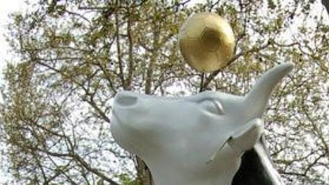 Umělohmotná kráva ve fotbalovém dresu s vlajkami účastnických zemí mistrovství světa.