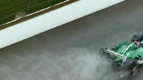 Jaguar Marka Webbera (nahoře) a mclaren Kimiho Räikkönena za sebou nechávají mokrý chvost při průjezdu cílovou rovinkou v Indianapolis.