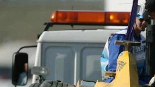 Mechanici nakládají monopost Brita Ralfa Firmana po havárii v tréninku na Velkou cenu Maďarska.
