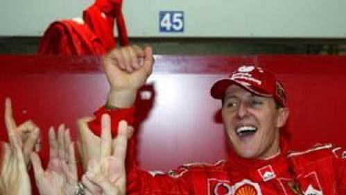 Michael Schumacher na ramenou svých mechaniků.