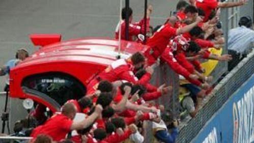 Rubens Barrichello jako první v cíli Velké ceny Británi za jásotu členů týmu Ferrari.