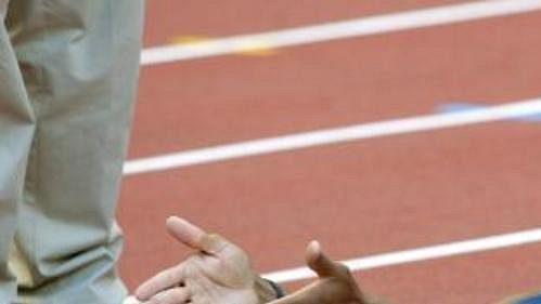 Americký sprinter Jon Drummond leží na dráze a diskutuje s organizátory.