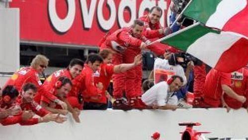 Michael Schumacher projíždí kolem členů stáje Ferrari po vítězství ve Velké ceně Japonska.