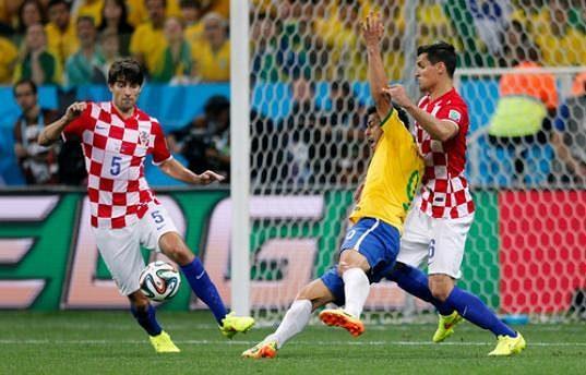 Brazilský útočník Fred (ve žlutém dresu) padá k zemi po souboji s chorvatským stoperem Dejanem Lovrenem (vpravo). Japonský sudí Nišimura následně nařídil pokutový kop pro domácí Kanárky.