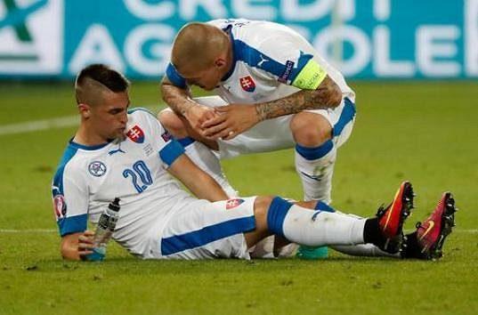 Slovenský obránce Martin Škrtel se sklání nad spoluhráčem Róbertem Makem.