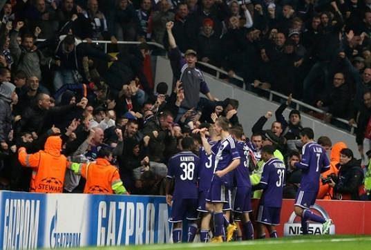 Fotbalisté Anderlechtu slaví s fanoušky vyrovnávací gól Aleksandara Mitroviče na stadiónu Arsenalu v Lize mistrů.