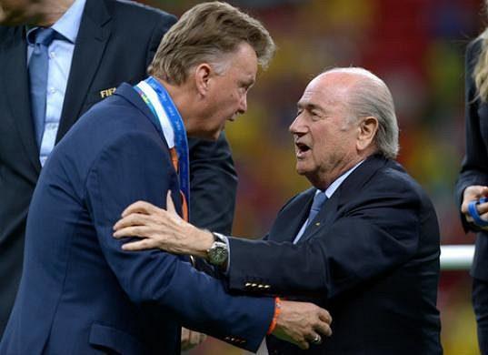 Kouč Nizozemců Louis van Gaal (vlevo) dostává bronzovou medaili z rukou prezidenta FIFA Seppa Blattera.